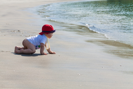 Baby crawling with determination on an untouched beach towards the water