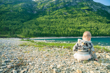 Baby sitting on a rocky beach of a mountain lake viewed from the back