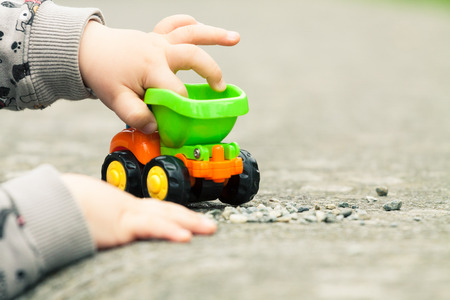 Close up of a boy's hands playing with a toy truck outside
