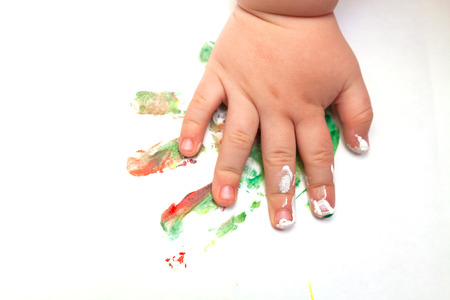 Close up of baby's hand covered with paint and a colorful imprint on white paper