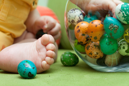 Close up of foot of baby playing with colorful Easter quail eggs