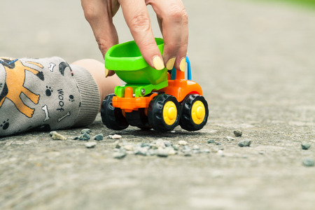 Close up of hands of mother and son playing with a toy truck and small stones Standard-Bild