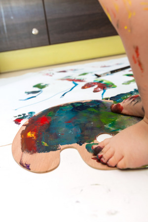 Close up of toddler's feet on a colorful palette with painted paper around Standard-Bild
