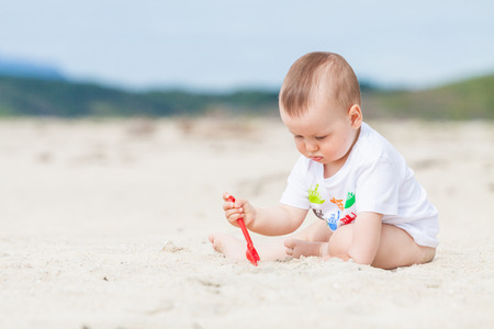 Cute baby exploring the sand on the beach with a toy shovel with mountains in the background Standard-Bild