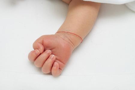 Hand van een slapende pasgeboren baby met rode draad om zijn pols voor bijgelovige bescherming Stockfoto