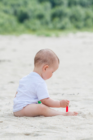 Sweet baby with t-shirt and toy shovel on the beach