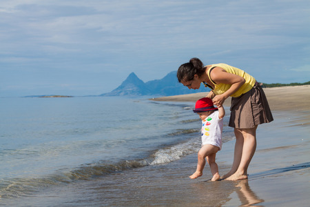 Toddler exploring the freezing water on an empty beach in Northern Norway with his mother