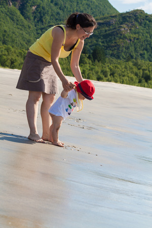 Toddler walking with his mother towards the water on an empty beach with forest and mountain on the background