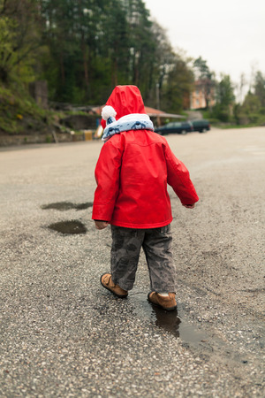 Toddler with red rain jacket walking in the puddles