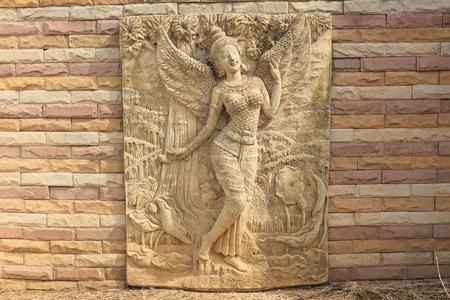 Kinnara statue on the wall photo