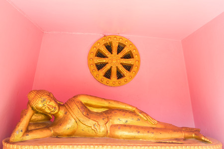 lie down: the lie down buddha statue  with the pink color background Stock Photo