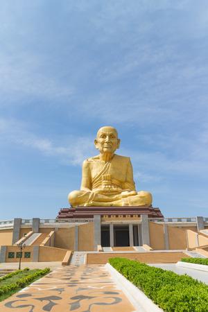 pu: Monk statue Luang Pu Thuad sitting under sunlight Stock Photo