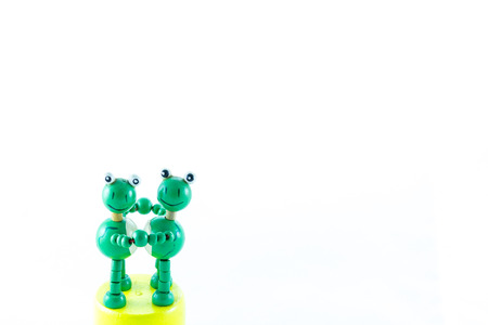 craving: frogs wood craving toy dancing on the white background