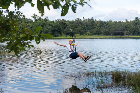 Young man crossing a lake in zip line Stock Photo