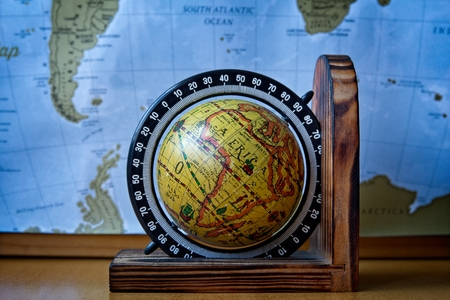 Map of Africa on an ancient wooden globe with world map in the background