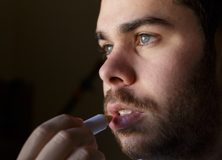 Young man with a beard repairing his damaged lips with moisturizer Imagens