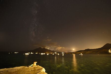 Milky Way, full moon and reflections in the sea at the pier of Isleta del Moro, Almeria, Spain.