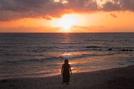 Woman watching the sunrise, sunset from the shore in Nijar, Almeria, Andalusia, Spain.