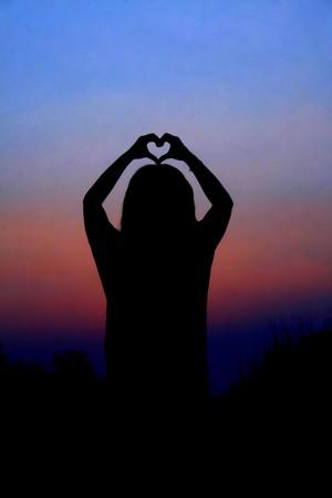 mano de dios: Manos de coraz�n al atardecer.  Foto de archivo