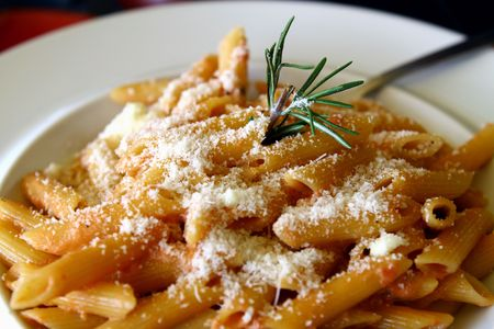 Penne pasta with cheese ,served on a white plate
