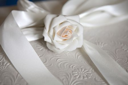 White rose and ribbon on a elegant wedding gift box photo