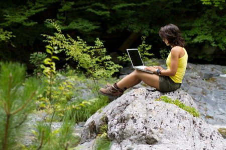 computer model: Girl with a laptop, sitting on a rock,  in the forest