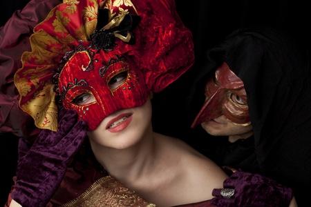 drama masks: Woman and man wearing carnival masks