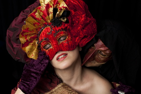 Woman and man wearing carnival masks