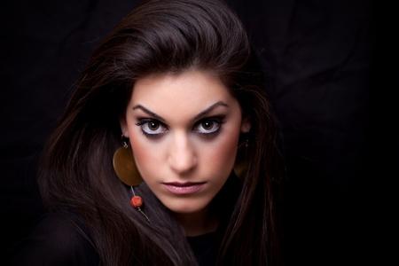 Attractive young woman posing, looking straight in the eyes, studio shot