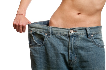 Young woman wearing her old jeans, showing her body after losing weight