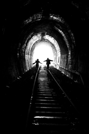 darkness: man and woman going towards the light, on railway tracks (black and white photograph with a little grain)