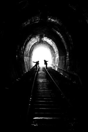 男と女の古い鉄道トラック (小さな粒で白黒写真) の光に向かって行く 写真素材