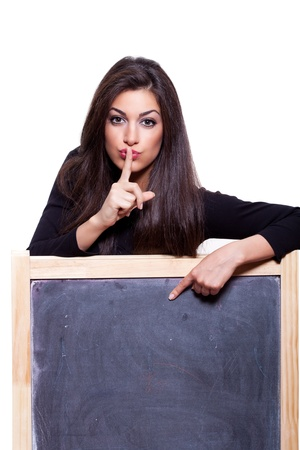Keep it secret. Attractive young woman, pointing at a blank blackboard. Studio shot, on white background Stock Photo - 11850017