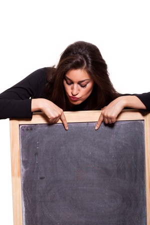 Attractive young woman pointing at a blank blackboard  on white background Stock Photo - 13094764