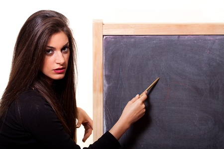 Young woman pointing at a blank blackboard with a pen  On white background Stock Photo - 13094763