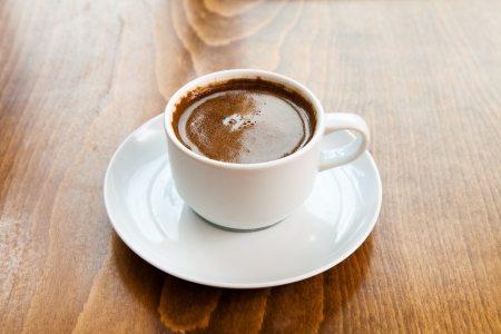 Greek turkish coffee served in a white cup on wooden table photo