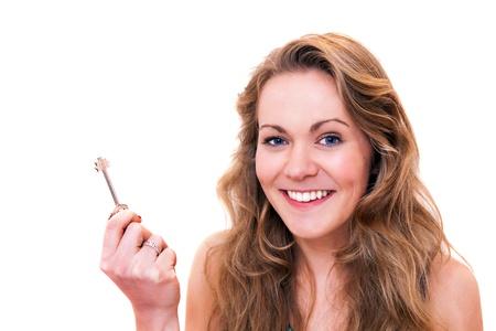 doorkey: Felice giovane donna sorridente che tiene la chiave della porta della sua nuova casa. Concetto di acquisto casa di propriet� Archivio Fotografico