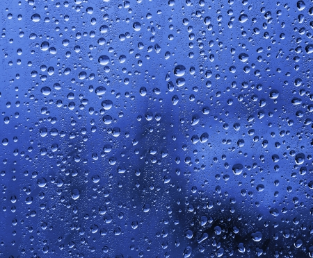 Raindrops on glass, in blue photo