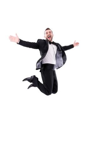 人間笑うとジャンプし、彼の成功を楽しんでいる - 黒のタキシードを身に着けているパピヨン ネクタイ、白い背景 - 本当の笑い、実際ジャンプで隔