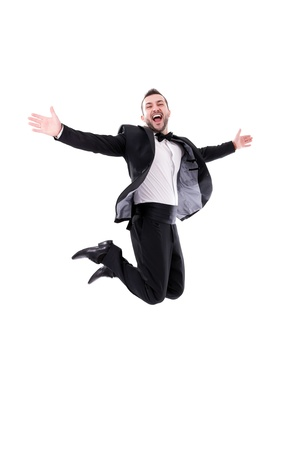 Man Laughing and Jumping Up, Enjoying His Success - Wearing black tuxedo and papillon tie, isolated on white background - Real laugh, real jump     Standard-Bild
