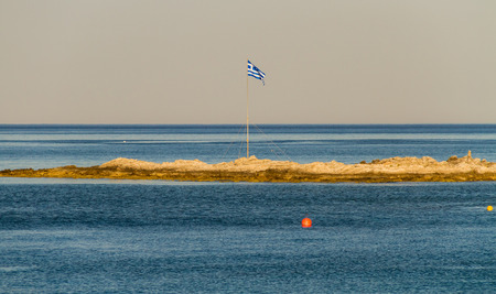 greece flag: Greek flag on small piece of land in the sea