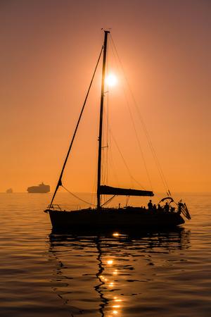 voilier ancien: Bateau à voile avant l'heure du coucher du soleil, dans l'eau de mer tranquille