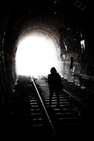tunel: Woman Silhouette Standing at Bright Light and the End of an Old Railway Tunnel Stock Photo