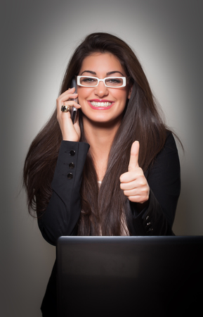 Successful Smiling Young  Businesswoman wearing white glasses, talking to phone and gives Thumbs Up, on grey background photo
