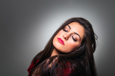 Portrait of Gorgeous Young Woman with Closed Eyes, Profile On Grey Background with copy space photo