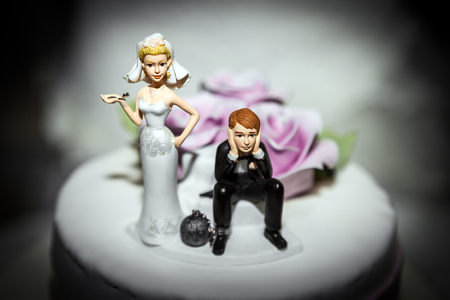 vows: Miniature of Bride and Groom on Wedding cake, with man having a  ball and chain on leg and woman holding the key... Comic Concept of Marriage Vows