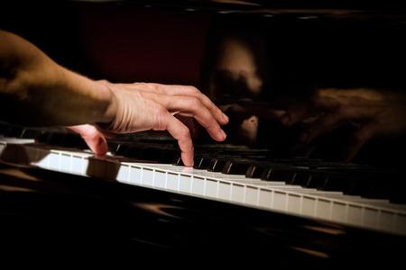 콘서트에서 피아노 연주, 오른손에 초점, 저조도 조건에서 닫습니다.