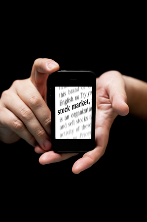 technology market: Hands Holding Smartphone, showing  the words Stock Market   printed, a concept of mobile and technology use nowadays     (on black background with very shallow depth of field)