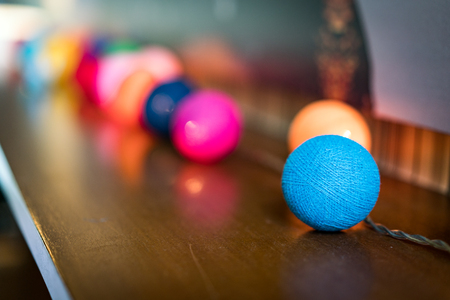 Decoration Detail of Coloful Small Spheres with light inside them, on wooden table