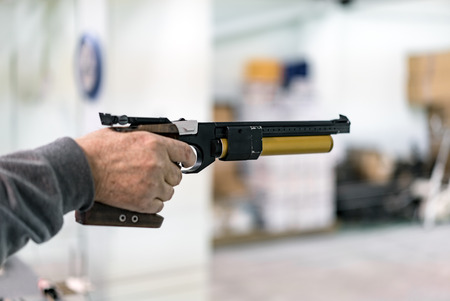Aiming the target and Shooting with Pistol, Indoors Stock Photo - 89880446